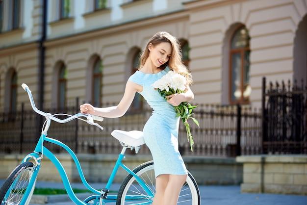 Close-up de um jovem modelo posando com peônias perto de uma bicicleta vintage no fundo desfocado de um edifício antigo