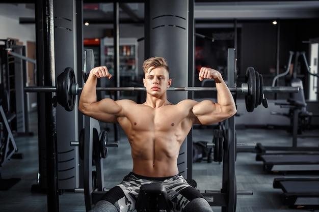 Close up de um jovem musculoso levantando pesos no ginásio em fundo escuro