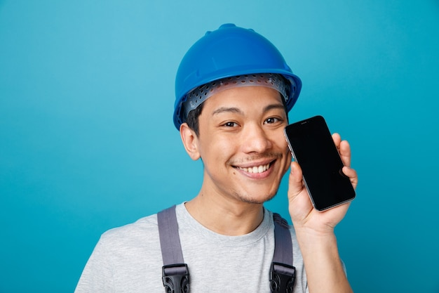 Close-up de um jovem trabalhador da construção civil sorridente, usando capacete de segurança e uniforme, segurando um telefone celular