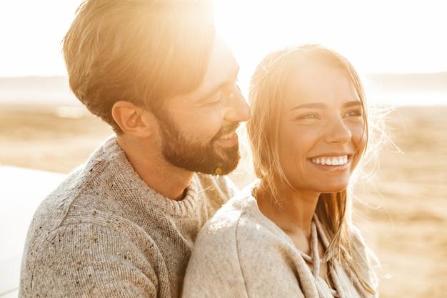 Close-up de um lindo casal jovem sorridente se abraçando em pé na praia