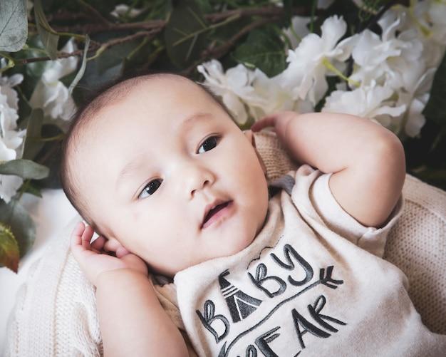 Close-up de um lindo menino branco rodeado de flores