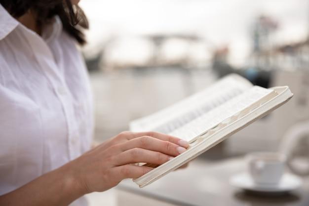 Close up de um livro em mãos femininas