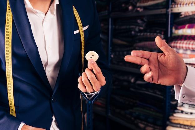 Close-up, de, um, macho, alfaiate, mostrando, botão, para, seu, cliente, gesticule, em, seu, loja