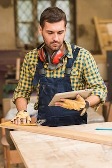 Close-up, de, um, macho, carpinteiro, olhar, tablete digital, medindo, a, madeira, bloco