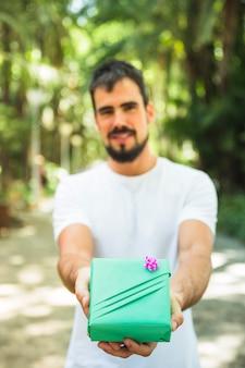 Close-up, de, um, mão homem, segurando, caixa presente verde