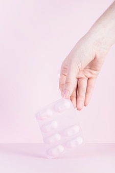 Close-up, de, um, mão mulher, segurando, cor-de-rosa, bolha, contra, fundo cor-de-rosa