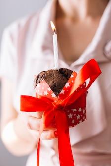Close-up, de, um, mão mulher, segurando, cupcake, com, iluminado, vela