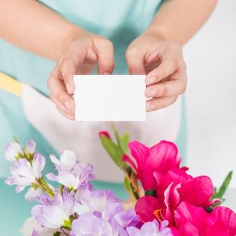 Close-up, de, um, mão mulher, segurando, em branco, visitando, cartão, sobre, colorido, flores