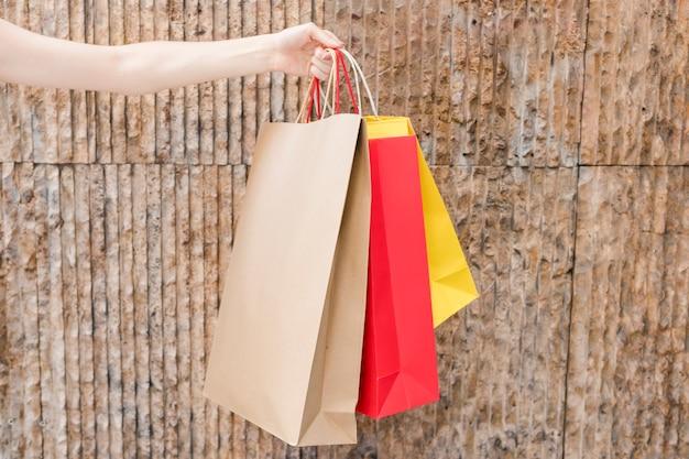 Close-up, de, um, mão mulher, segurando, multi coloriu, bolsas para compras, frente, marrom, parede