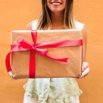 Close-up, de, um, mão mulher, segurando, presente, amarrado, com, fita vermelha