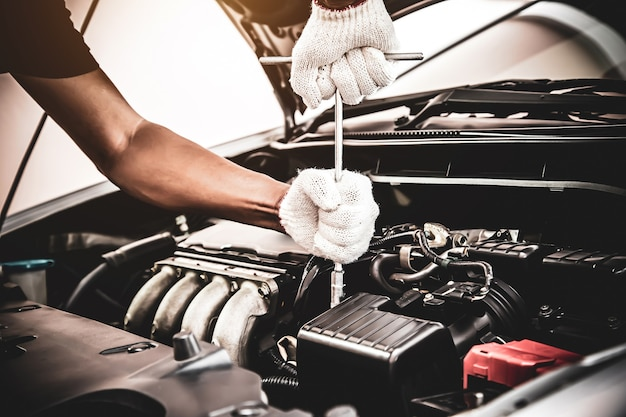 Close-up de um mecânico de automóveis usando uma chave inglesa para consertar o motor de um carro