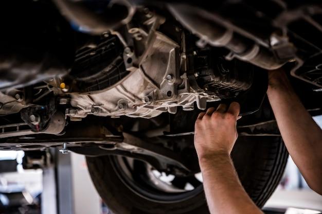 Close up de um mecânico que conserta um carro levantado