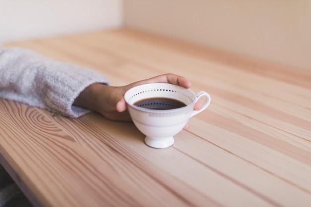 Close-up, de, um, menina, mão, segurando, xícara café, ligado, escrivaninha madeira