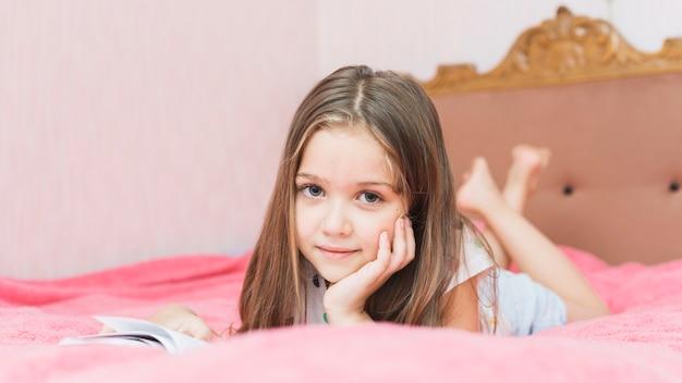 Close-up, de, um, menina, mentindo, ligado, cor-de-rosa, cama, livro leitura