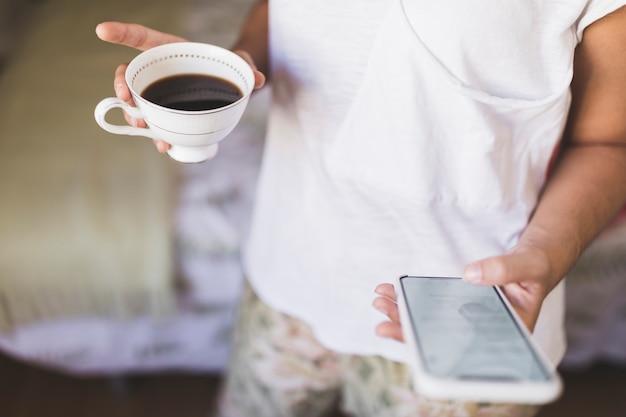 Close-up, de, um, menina, xícara café segurando, usando, smartphone