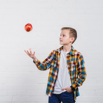Close-up, de, um, menino, com, seu, passe bolso, jogando maçã vermelha, em, ar, contra, fundo branco