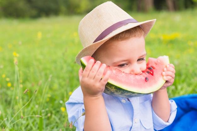 Close-up, de, um, menino, comendo melancia, fatia, parque