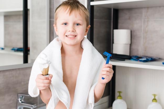 Close-up, de, um, menino sorridente, ficar, em, a, banheiro, segurando, raspa escova, e, azul, navalha, em, mão