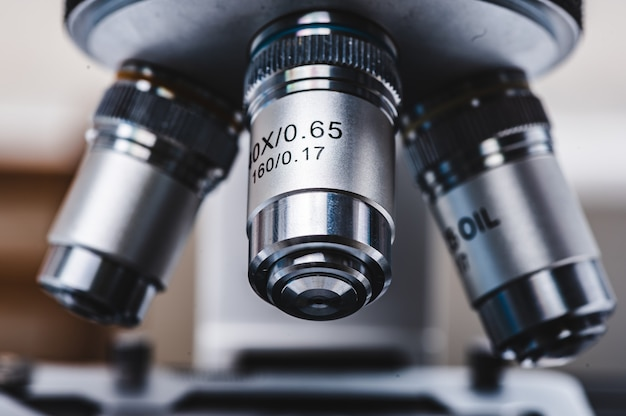 Close-up de um microscópio científico profissional com lente de metal no laboratório médico