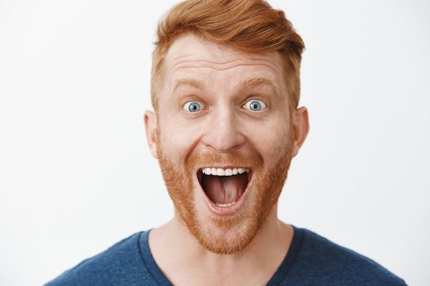 Close-up de um modelo adulto ruivo surpreso e alegre com a barba sorrindo amplamente, com o queixo caído e uma expressão impressionada, satisfeito e emocionado com o evento positivo sobre a parede cinza
