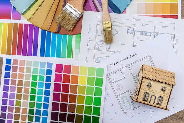 Close up de um modelo de casa de madeira com planta e amostras de cores
