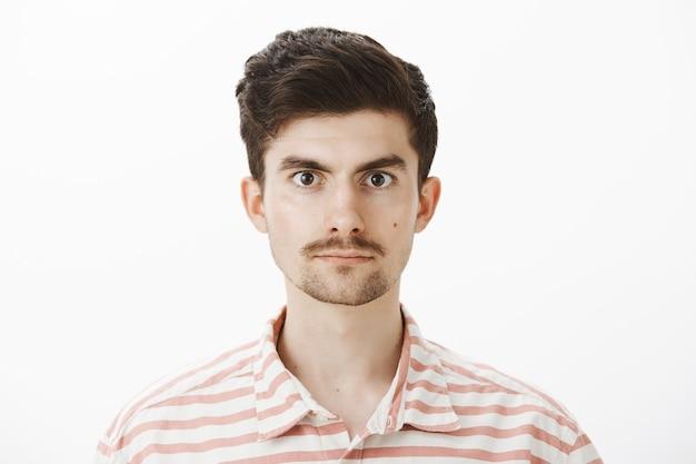 Close-up de um modelo masculino caucasiano calmo e confiante com uma camisa listrada, em pé casualmente, autoconfiante enquanto se oferece para doar sangue