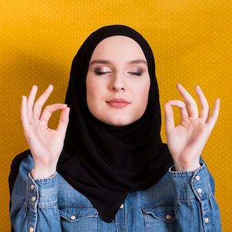 Close-up, de, um, mulher, com, headcover, gesticule, tá bom sinal, e, meditar, sobre, fundo