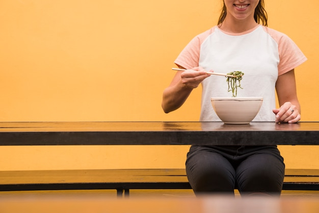 Close-up, de, um, mulher, comer, verde, algas, com, chopsticks, ligado, tabela madeira, contra, amarela, fundo
