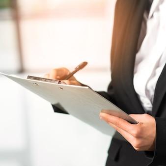 Close-up, de, um, mulher, escrita, ligado, área de transferência, com, caneta