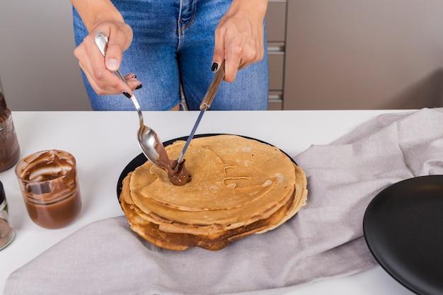Close-up, de, um, mulher, espalhar, a, manteiga amendoim, ligado, panqueca, com, colher, e, faca