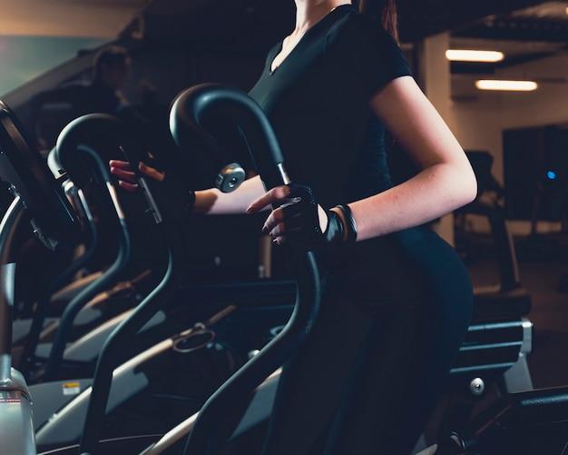 Close-up, de, um, mulher, exercitar, ligado, elíptico, cardio, máquina