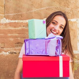 Close-up, de, um, mulher feliz, segurando, empilhado, presentes