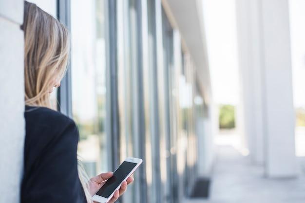 Close-up, de, um, mulher, inclinar-se, parede, usando, telefone móvel