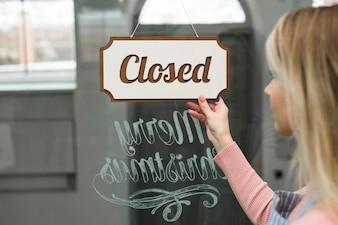 Close-up, de, um, mulher olha, em, fechado, tag, pendurar, um, vidro, de, storefront