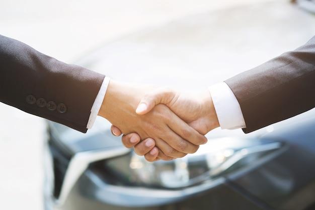 Close-up de um negociante de homem de negócios oferece um carro para um novo proprietário
