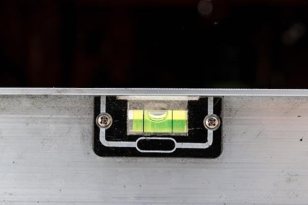 Close-up de um nível de metal de construção, uma régua deitada nas placas.