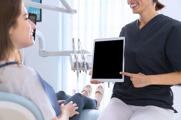 Close-up, de, um, odontólogo, apontar, ligado, tablete digital, tela, para, femininas, paciente