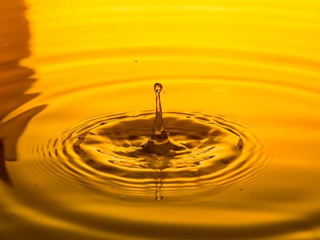 Close up de um óleo de gota em um fundo amarelo