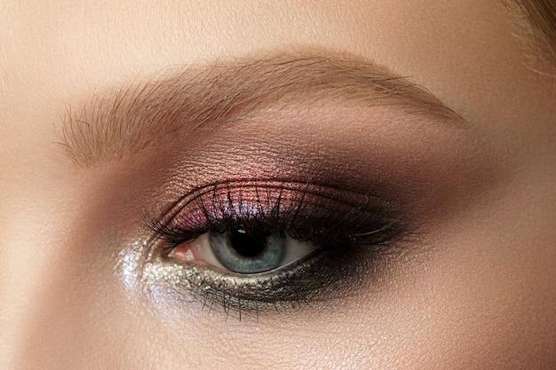 Close-up de um olho de mulher azul com uma bela maquiagem marrom com tons de vermelho e laranja