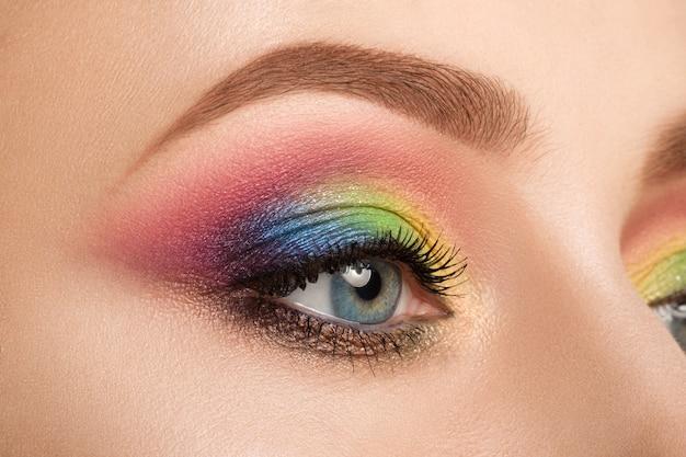 Close-up de um olho feminino azul com uma bela e moderna maquiagem criativa