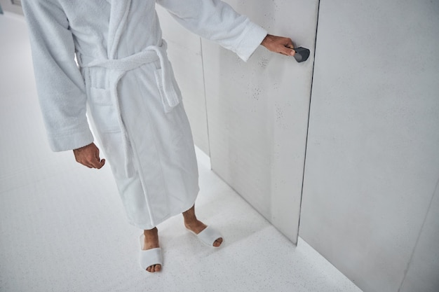 Close-up de um paciente do sexo masculino com roupão branco, segurando a maçaneta da porta na clínica de bem-estar