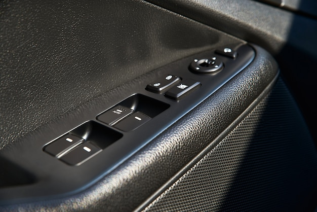 Close up de um painel de controle da porta em um carro novo. apoio de braço com painel de controle da janela, botão de trava da porta e espelho