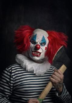 Close-up de um palhaço assustador com cabelos ruivos, olhos brancos, dentes ensangüentados, machado na mão e um olhar ameaçador
