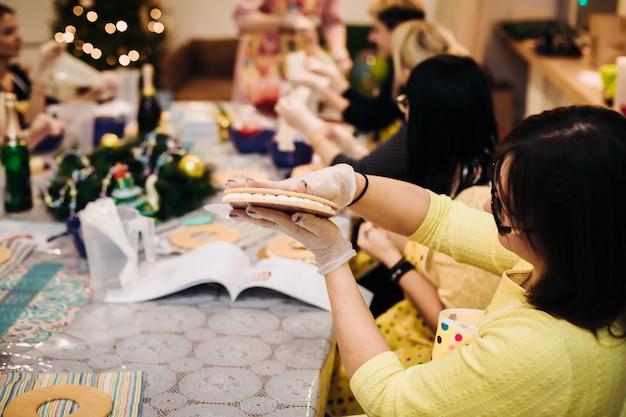 Close-up de um pão de mel de natal nas mãos de um chef pasteleiro, uma vista por cima do ombro. ambiente de trabalho