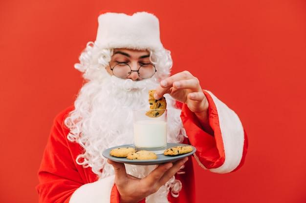 Close-up de um papai noel segurando um prato com biscoitos e um copo de leite
