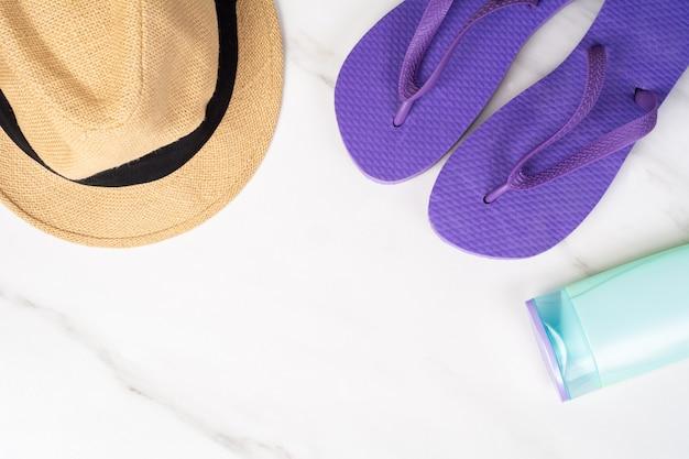 Close-up de um par de chinelos, chapéu e protetor solar