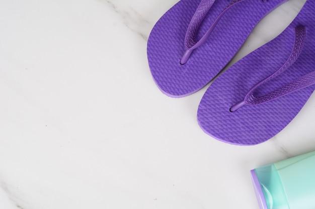 Close-up de um par de flip-flops e protetor solar.
