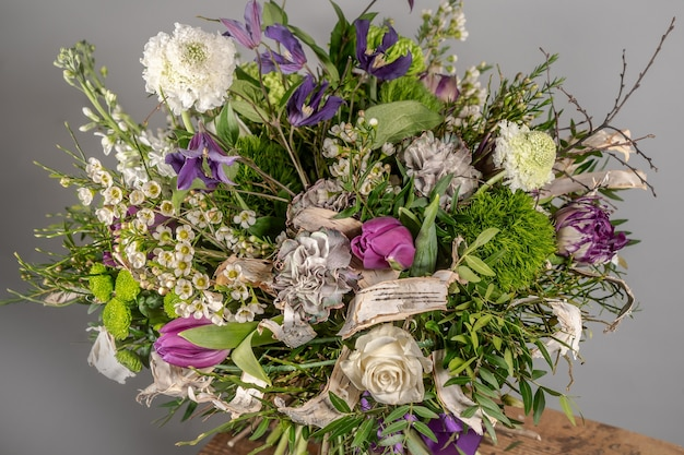 Close-up de um pequeno buquê de flores rosa em vaso de vidro com fundo cinza turva. casamento ou aniversário, conceito de dia dos namorados.