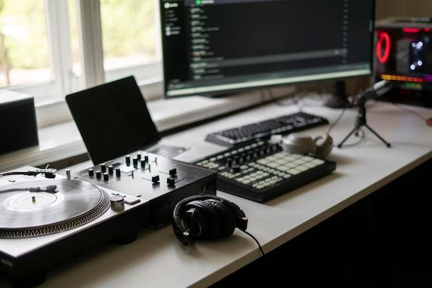 Close-up de um pequeno estúdio de produção musical, toca-discos, mixer de bateria midi e microfone
