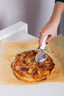 Close-up, de, um, pessoa, corte, a, pizza, com, cortador, ligado, papel pergaminho
